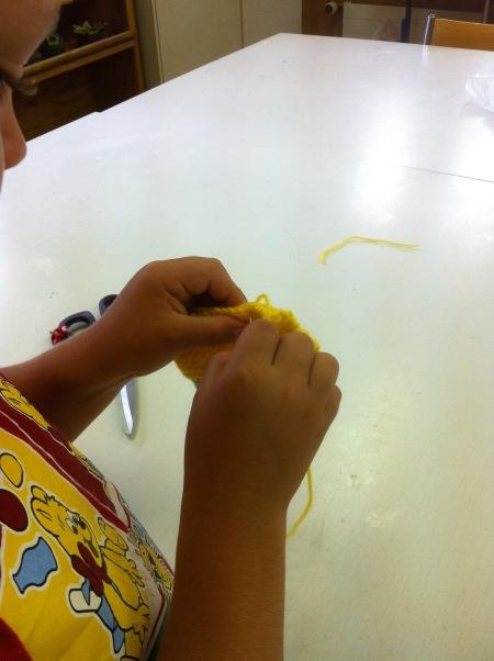 Den gestrickten Lappen zusammennähen. / Stitching the knitted cloth together.