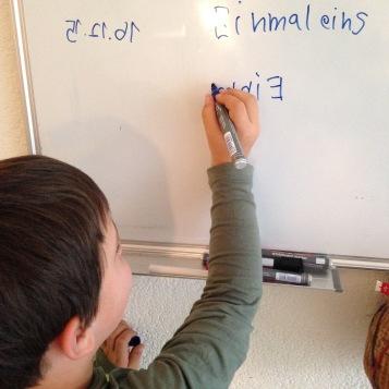 Erstes Probieren an der Tafel / First letters on the whiteboard